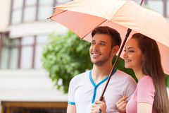 Portrait of woman and man standing under umbrella. Stock Photos