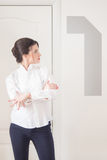 Portrait of woman manager on white background. Portrait of young excited brunette woman standing next to big figure one on a white background stock photography
