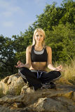 Portrait woman meditating yoga on rock Royalty Free Stock Photos