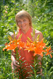Portrait of the woman of middle age with orange lilies Royalty Free Stock Photos