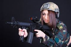 Portrait of a woman in a military uniform with an assault rifle Royalty Free Stock Photo
