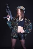 Portrait of a woman in a military uniform with a submachine gun Stock Photography