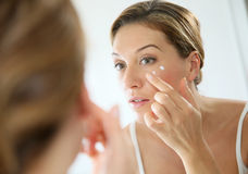 Portrait of a woman in the mirror applying a cream Royalty Free Stock Photo