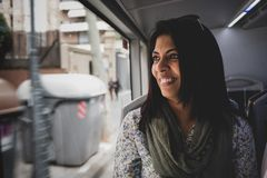 Portrait of a woman in a moving bus. Portrait of a woman of Indian ethnicity looking out of the window of a moving bus - with copy space stock photos