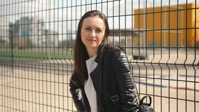 The woman standing at the mesh fence near the Playground and looking at the camera. Portrait of woman near fence mesh. Woman looking at the camera leaning on stock video footage