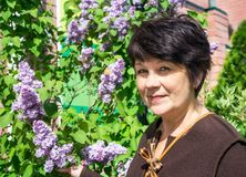 Portrait of woman near lilac Royalty Free Stock Image