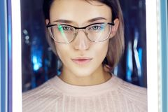 Portrait of a woman in neon colored reflection glasses in the background. Good vision, perfect makeup on girl face. Art portrait. Of a flare and bokeh on the royalty free stock images