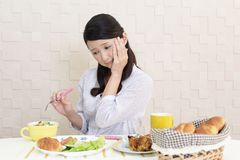 Woman with no appetite. Portrait of woman with no appetite in front of the meal stock photo