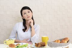 Woman with no appetite. Portrait of woman with no appetite in front of the meal royalty free stock images