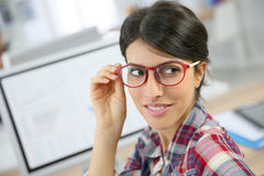 Portrait of woman office worker in front of computer. Portrait of office worker with eyeglasses on Stock Photography
