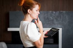 Portrait of a woman office worker holding calculator. Royalty Free Stock Images