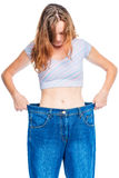 Portrait of a woman in old big jeans after losing weight. On a white background Stock Photo
