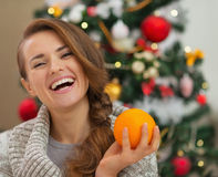 Portrait of woman with orange near Christmas tree Stock Photos
