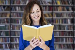 Portrait of woman over 25 in a library reading an opened book, concentrated and smart. Young college student in co-working royalty free stock image