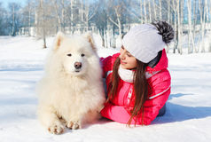 Portrait woman owner with white Samoyed dog lying on snow winter Royalty Free Stock Photo