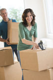 Portrait Of Woman Packing Cardboard Box At Home Stock Images