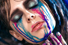 Portrait of a woman with painted face. Creative makeup and bright style. Royalty Free Stock Image