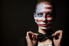 Portrait of woman with painted USA Flag and bow tie. On black stock photo