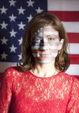 Portrait of woman with painted USA flag. On american flag background stock photography