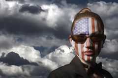 Portrait of woman with painted USA flag and sunglasses. On dramatic sky royalty free stock photo