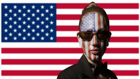 Portrait of woman with painted USA flag and sunglasses. On usa background royalty free stock photo