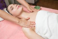 Portrait of woman patient in ayurveda spa wellness center lying relaxed. On wood with aroma spa accessories. Young beautiful indian girl with ideal clean skin royalty free stock image