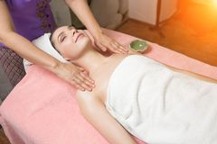Portrait of woman patient in ayurveda spa wellness center lying relaxed. On wood with aroma spa accessories. Young beautiful indian girl with ideal clean skin royalty free stock photo