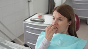 Portrait of woman patient in dental clinic. Waiting in dental chair for stomatologist. Dental check up. Woman patient in dental clinic. Waiting in dental chair stock video footage