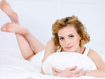 Portrait of woman with pillow. Portrait of young blond beautiful woman with pillow - indoors Stock Photography