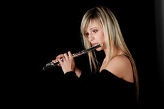 Portrait of a woman playing transverse flute. Isolated on black Stock Photo