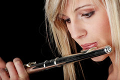 Portrait of a woman playing transverse flute. Isolated on black Stock Images