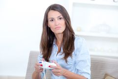Portrait woman playing video games against gray background. Portrait of woman playing video games against gray background Stock Photography
