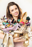 Portrait of the woman with plenty of shoes Royalty Free Stock Images