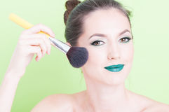 Portrait of woman posing with  professional brush make-up. Isolated on green background Royalty Free Stock Photography