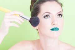 Portrait of woman posing with  professional brush make-up. Isolated on green background Stock Images
