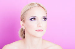 Portrait of woman posing with  professional trendy make-up. Looking up  on pink background with copy text space Royalty Free Stock Images