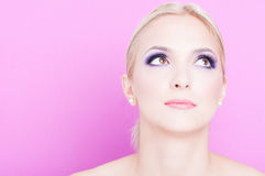 Portrait of woman posing with  professional trendy make-up. Looking up  on pink background with copy text space Royalty Free Stock Photo