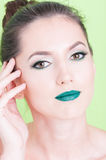 Portrait of woman posing with trendy professional make-up. Isolated on green background Stock Photography