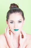 Portrait of woman posing with trendy professional make-up. Isolated on green background Stock Photo