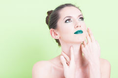 Portrait of woman posing with trendy professional make-up. Looking up isolated on green background with copy text area Stock Images