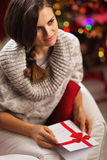 Portrait of woman with postcard in front of christmas lights Stock Photos