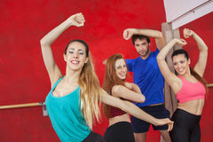 Portrait Of Woman Practicing Zumba With Friends. Portrait of happy young women practicing Zumba with friends in gym Royalty Free Stock Images