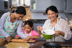 Portrait of woman preparing food with family in kitchen. Portrait of mature women preparing food with family in kitchen at home stock photography