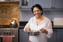 Portrait of woman preparing food in kitchen Stock Images