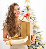 Portrait of woman with present boxes near christmas tree. Portrait of young woman with christmas present boxes in front of christmas tree Stock Photography