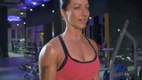 Portrait of the woman pumping biceps. Close up woman doing bodybuilding exercise pumping biceps lifting barbell. Athlete in the gym. Fitness, sport, and training stock footage