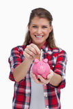 Portrait of a woman putting a note a piggy bank Royalty Free Stock Photos