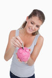 Portrait of a woman putting a note in a piggy bank Royalty Free Stock Image