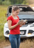 Portrait of woman reading owner manual at broken car in meadow. Portrait of young woman reading owner manual at broken car in meadow stock image