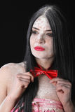 Portrait of a woman in a red bow-tie covered by white powder Stock Images